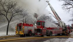 Firefighters work the scene where a fire engulfed several apartment units in the Cedar Riverside neighborhood in Minneapolis on Jan. 1, 2014. Authorities say at least 13 people have been hurt. (Associated Press/Star Tribune, McKenna Ewen)