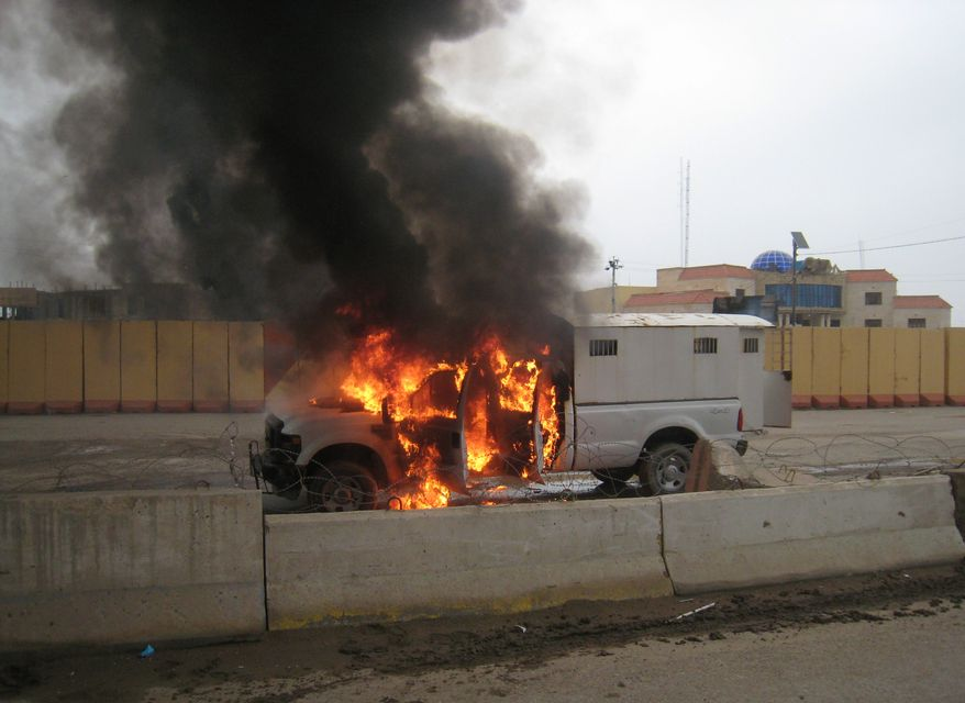 ** FILE ** A police truck full of prisoners being transported was set afire by al Qaeda fighters after they freed prisoners in front of the main provincial government building, in Fallujah, 40 miles (65 kilometers) west of Baghdad, Iraq, Wednesday, Jan. 1, 2014. (AP Photo)