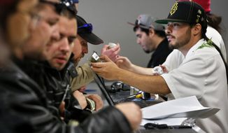 "** FILE ** Employee David Marlow, right, helps a customer, who smells a strain of marijuana before buying it, at the crowded sales counter inside Medicine Man marijuana retail store, which opened as a legal recreational retail outlet in Denver on Wednesday, Jan. 1, 2014. Colorado began retail marijuana sales on Jan. 1, a day some are calling ""Green Wednesday."" (AP Photo/Brennan Linsley)"