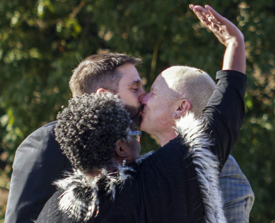 "Danny Leclair, rear left, kisses his partner Aubrey Loots, right, as the couple from Los Angeles were married  by Rev. Alfreda Lanoix, center, of the Unity Fellowship Church of Christ aboard the AIDS Healthcare Foundation's float  ""Living the Dream""  during the 125th Tournament of Roses Parade in Pasadena, Calif., Wednesday, Jan. 1, 2014.   (AP Photo/Ringo H.W. Chiu)"