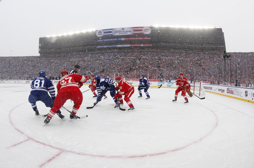 The Toronto Maple Leafs and the Detroit Red Wings face off during the first period of the Winter Classic outdoor NHL hockey game at Michigan Stadium in Ann Arbor, Mich., Wednesday, Jan. 1, 2014. (AP Photo/Paul Sancya)