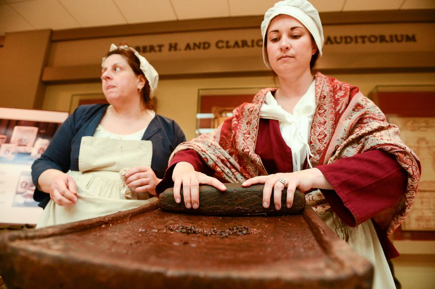 Historic Trades Interpreters Melissa Reed, left, and Trish Kristoff make drinking chocolate using 18-century techniques as part of Christmas at George Washington's Mount Vernon, Mount Vernon, Va., Monday, December 16, 2013. Mount Vernon celebrates Christmas with Christmas trees, 18th-century chocolate making, Christmas dancing and story telling, as well as Aladin the Camel. (Andrew Harnik/The Washington Times)