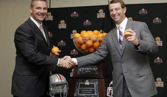 Ohio State head coach Urban Meyer, left, and  Clemson head coach Dabo Swinney pose for photographers with the Orange Bowl trophy in Fort Lauderdale, Fla., Thursday, Jan. 2, 2014. Ohio State will face Clemson in the NCAA college football Orange Bowl classic, Friday, Jan. 3, in Miami Gardens, Fla. (AP Photo/Alan Diaz)