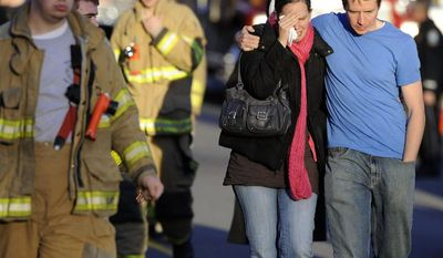 FILE - In this Dec. 14, 2012 file photo, Robert and Alissa Parker, at right, leave a firehouse staging area following a shooting at the Sandy Hook Elementary School in Newtown, Conn. Gunman Adam Lanza opened fire inside the school, killing 26 children and adults, including the Parkers' daughter Emilie Parker, 6. (AP Photo/Jessica Hill, File)