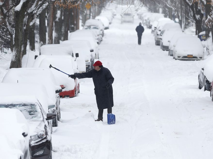 A man clears snow from a vehicle on Friday, Jan. 3, 2014, in Albany, N.Y.  A winter storm slammed into the U.S. Northeast with howling winds and frigid cold, dumping nearly two feet (60 centimeters) of snow in some parts and whipping up blizzard-like conditions Friday. (AP Photo/Mike Groll)