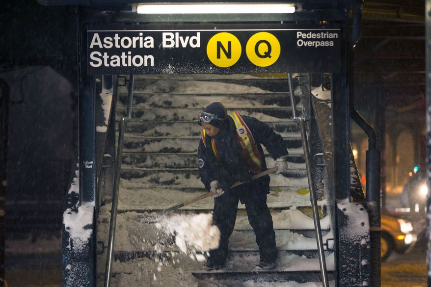 A worker clears snow from a stairway at the Astoria Blvd subway station, Friday, Jan. 3, 2014, in the Queens borough of New York. New York City public schools were closed Friday after up to 7 inches of snow fell by morning in the first snowstorm of the winter. (AP Photo/John Minchillo)