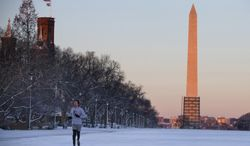 A jogger runs on the National Mall, with the Washington Monument in the background, Friday, Jan. 3, 2014, in Washington. After a storm blew through the Washington region overnight, roads are being cleared and many schools systems are closed. The federal government and the District of Columbia government will be open Friday, but workers have the option to take leave or telework.  (AP Photo/ Evan Vucci)