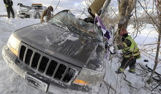 Tow operators work to salvage a wrecked Jeep as Fuller Hose Co. Lt. Chris Skrekla, right, searches for the vehicle identification number after two people were injured in a rollover accident on westbound Interstate 90 just west of the Bort Road overpass in North East Township, near Erie, Pa. on Friday, Jan. 3, 2014. Pennsylvania State Police responded to numerous accidents in the area early Friday due to wintry weather.   (AP Photo/Erie Times-News, Greg Wohlford) TV OUT; MAGS OUT