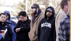 Boeing machinists stand in a line of several hundred as they wait to cast their ballots on Friday, Jan. 3, 2014, in Everett, Wash. Boeing machinists decide Friday whether to accept a contract that would concede some pension and health care benefits in order to secure assembly of the company's new 777X airplane in Washington state. (AP Photo/Elaine Thompson)