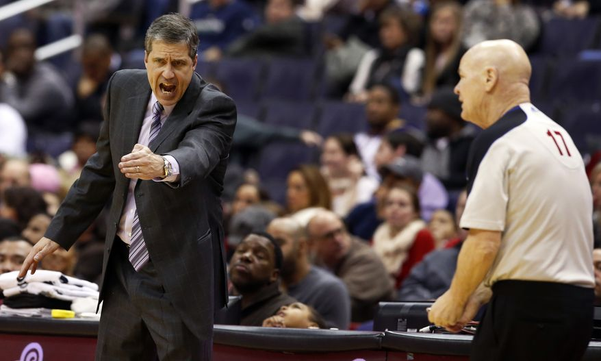 Washington Wizards head coach Randy Wittman, left, makes his point to referee Joe Crawford (17) in the second half of an NBA basketball game against the Toronto Raptors, Friday, Jan. 3, 2014, in Washington. The Raptors won 101-88. (AP Photo/Alex Brandon)