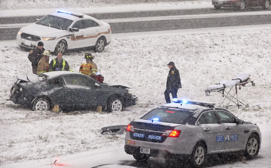 Law enforcement, fire and rescue workers prepare to remove an injured passenger from a car that was in an accident involving a tractor-trailer Thursday, Jan. 2, 2014, near Winchester,Va., as snow fell in the northern Shenandoah Valley. (AP Photo/The Winchester Star, Scott Mason)