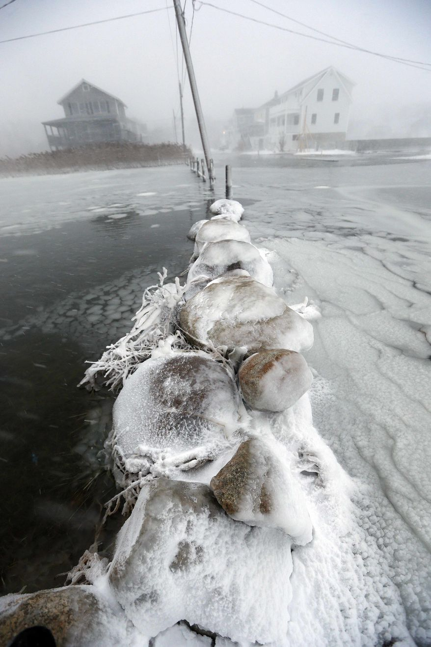 Floodwaters surround a stone wall along the shore in Scituate, Mass., Friday, Jan. 3, 2014. A winter storm slammed into the U.S. Northeast with howling winds and frigid cold, dumping nearly 2 feet (60 centimeters) of snow in some parts and whipping up blizzard-like conditions Friday. (AP Photo/Michael Dwyer)