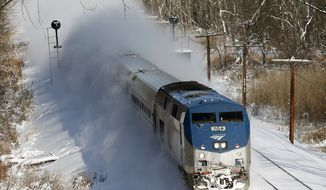 ** FILE ** An Amtrak train kicks up fresh snow as it speeds southbound on Friday, Jan. 3, 2014, in Schodack Landing, N.Y. (AP Photo/Mike Groll)