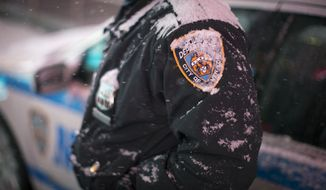 Snow accumulates on an NYPD officer in Times Square, Thursday, Jan. 2, 2014, in New York. The snow storm is expected to bring snow, stiff winds and punishing cold into the Northeast. (AP Photo/John Minchillo)