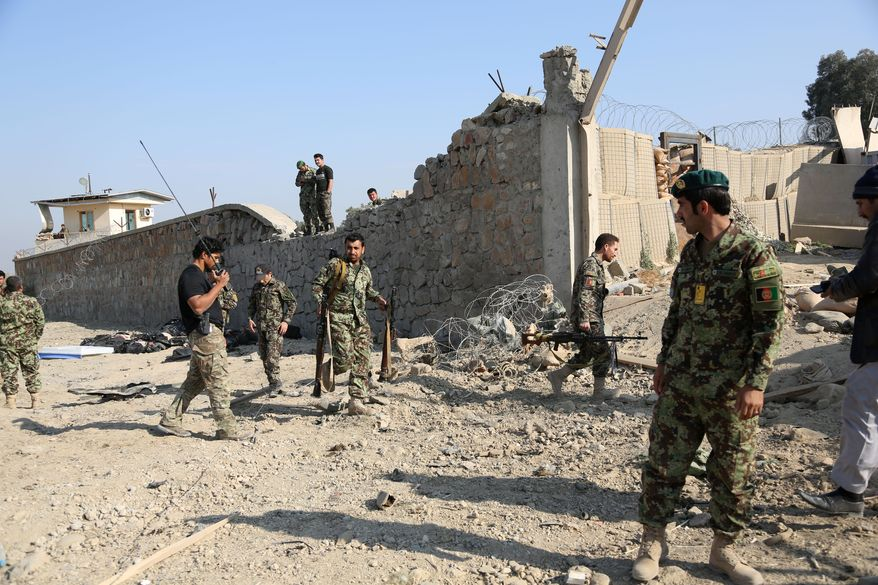 ** FILE ** Afghan officials investigate the site of a deadly suicide attack on a joint NATO-Afghan base in the Ghani Khail district of Nangarhar province, east of Jalalabad, Afghanistan, Saturday, Jan. 4, 2014. (AP Photo/Rahmat Gul)
