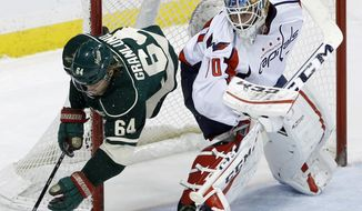 Minnesota Wild center Mikael Granlund (64), of Finland, falls behind Washington Capitals goalie Braden Holtby, right, while chasing the puck during the first period of an NHL hockey game in St. Paul, Minn., Saturday, Jan. 4, 2014. (AP Photo/Ann Heisenfelt)