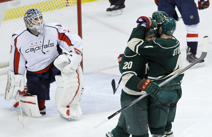 Minnesota Wild defenseman Clayton Stoner, right, hugs defenseman Ryan Suter (20) after he scored his third goal of the game, on Washington Capitals goalie Braden Holtby, left, during the third period of an NHL hockey game in St. Paul, Minn., Saturday, Jan. 4, 2014. The Wild won 5-3. (AP Photo/Ann Heisenfelt)