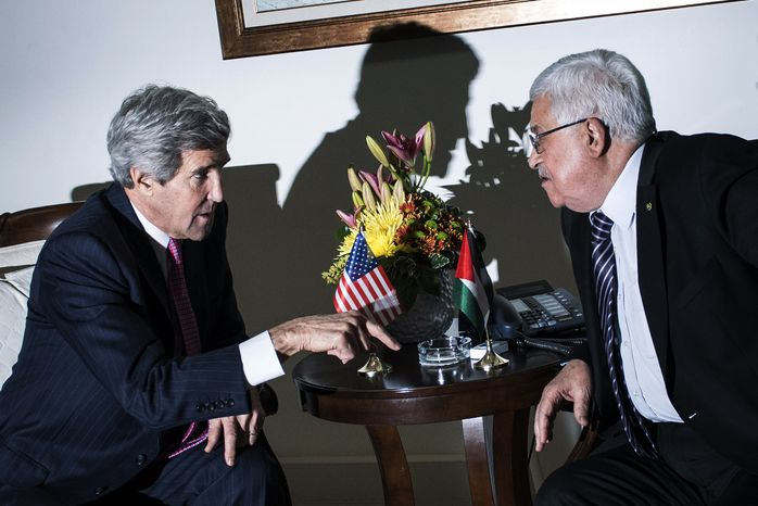 U.S. Secretary of State John Kerry, left, talks with Palestinian President Mahmoud Abbas at the presidential compound in the West Bank city of Ramallah on Saturday, Jan. 4, 2014. Kerry is on his 10th visit to the region to try to craft a peace treaty that would create a Palestinian state alongside Israel. (AP Photo/Brendan Smialowski, Pool)