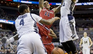 St. John's D'Angelo Harrison (11) is fouled as he shoots against Georgetown D'Vauntes Smith-Rivera (4) and Jabril Trawick (55) during the first half of an NCAA college basketball game in Washington, Saturday, Jan. 4, 2014.  (AP Photo/Manuel Balce Ceneta)
