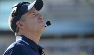 FILE - In htis Dec. 22, 2013, file photo, Tennessee Titans head coach Mike Munchak watches the stadium video monitor during the first half of an NFL football game against the Jacksonville Jaguars in Jacksonville, Fla.  A person familiar with the decision say Titans President Tommy Smith has fired  Munchak after three seasons as his head coach and 31 years combined with this franchise as a player and coach. The person spoke to The Associated Press on Saturday, Jan. 4, 2014, on the condition of anonymity because the Titans have not made an official announcement. (AP Photo/Phelan M. Ebenhack, File)