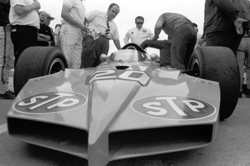 FILE - In this May 14, 1969, file photo, car owner Andy Granatelli, center left, and driver Art Pollard, center rear, examine Granatelli's newest car at the Indianapolis Motor Speedway in Indianapolis. Granatelli, the former CEO of STP motor oil company who made a mark on motorsports as a car owner, innovator and entrepreneur, died Sunday, Dec. 29, 2013.  He was 90.  (AP Photo/File)