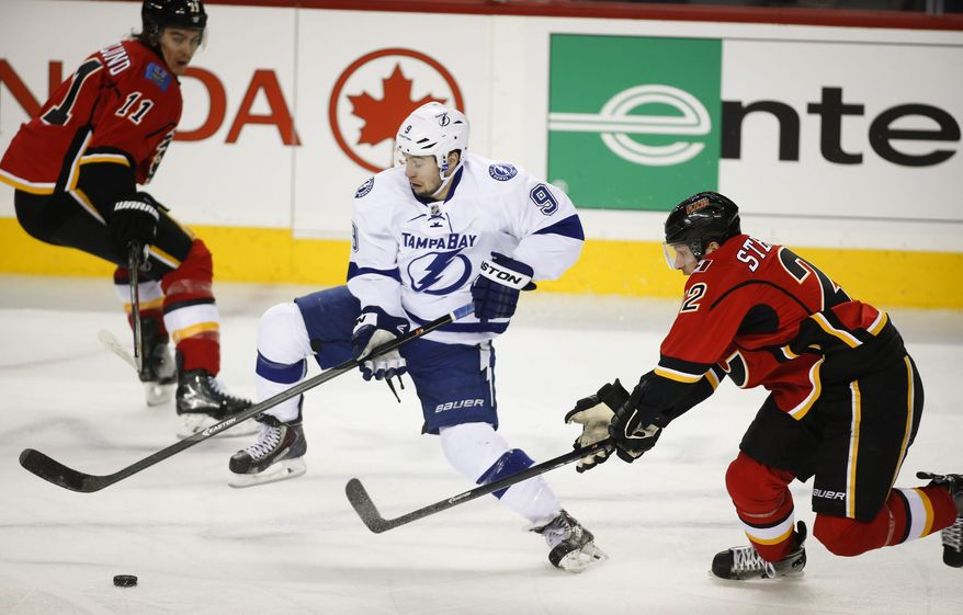 Tampa Bay Lightning's Tyler Johnson, center, chases the puck between Calgary Flames' Mikael Backlund, left, from Sweden, and Lee Stempniak during the first period of an NHL hockey game Friday, Jan. 3, 2014, in Calgary, Alberta. (AP Photo/The Canadian Press, Jeff McIntosh)