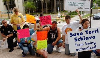 In this March 24, 2005, photo, demonstrators pray for Terri Schiavo outside the Pinellas County Courthouse in Clearwater, Fla. Schiavo, in a vegetive state, died after a seven-year legal fight by her husband to get her feeding tube removed. The legal fight prompted a national debate about the right to die. (AP Photo/Steve Nesius, File)