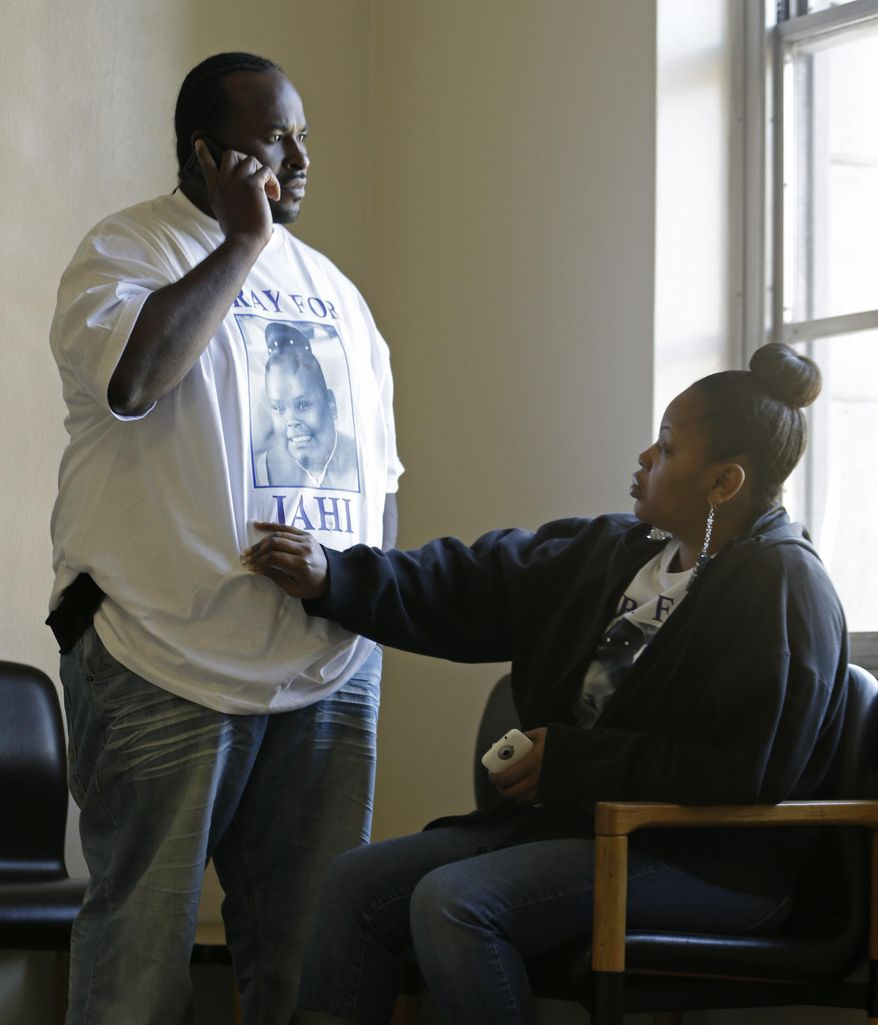 Nailah Winkfield, right, mother of 13-year-old Jahi McMath, touches her husband Martin Winkfield as they wait outside a courtroom Friday, Jan. 3, 2014, in Oakland, Calif. A federal magistrate was expected to meet Friday with lawyers to try to resolve a dispute over the care ofJahi McMath, who was declared brain dead after tonsil surgery. (AP Photo/Ben Margot)