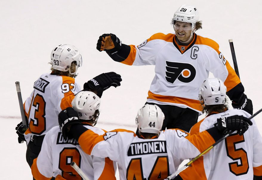 Philadelphia Flyers' Claude Giroux (28) smiles as he arrives to join the celebration of a goal by Jakub Voracek (93), of the Czech Republic, against the Phoenix Coyotes, with teammates Braydon Coburn (5), Kimmo Timonen (44), of Finland, and Steve Downie (9) during the third period of an NHL hockey game Saturday, Jan. 4, 2014, in Glendale, Ariz. The Flyers defeated the Coyotes 5-3. (AP Photo/Ross D. Franklin)