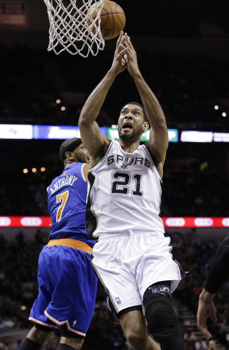 San Antonio Spurs' Tim Duncan (21) is blocked by New York Knicks' Carmelo Anthony (7) as he tries to score during the first half on an NBA basketball game, Thursday, Jan. 2, 2014, in San Antonio.  (AP Photo/Eric Gay)
