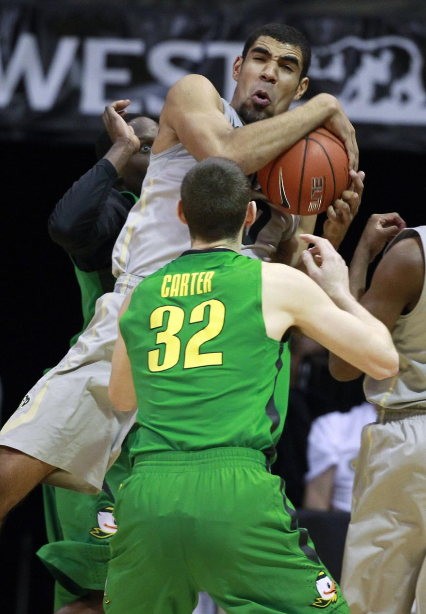 Colorado forward Josh Scott, back, pulls in a rebound as Oregon forward Ben Carter covers in the first half of an NCAA college basketball game, Sunday, Jan. 5, 2014, in Boulder, Colo. (AP Photo/David Zalubowski)