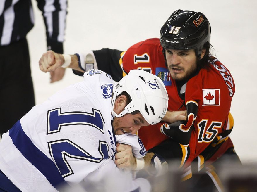 Tampa Bay Lightning's Ryan Malone, left, fights with Calgary Flames' Kevin Westgarth during the first period of an NHL hockey game Friday, Jan. 3, 2014, in Calgary, Alberta. (AP Photo/The Canadian Press, Jeff McIntosh)