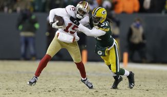 San Francisco 49ers wide receiver Michael Crabtree (15) runs against Green Bay Packers cornerback Davon House (31) after catching a pass from the 49ers quarterback Colin Kaepernick during the second half of an NFL wild-card playoff football game, Sunday, Jan. 5, 2014, in Green Bay, Wis. (AP Photo/Mike Roemer)