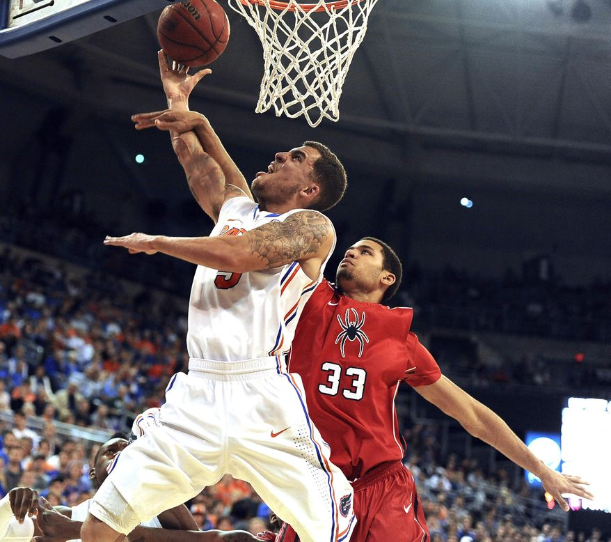 Florida's Scottie Wilbekin (5) shoots as Richmonds' Alonzo Nelson-Ododa defends during the first half of an NCAA college basketball game in Gainesville, Fla., Saturday, Jan. 4, 2014.  (AP Photo/Phil Sandlin)