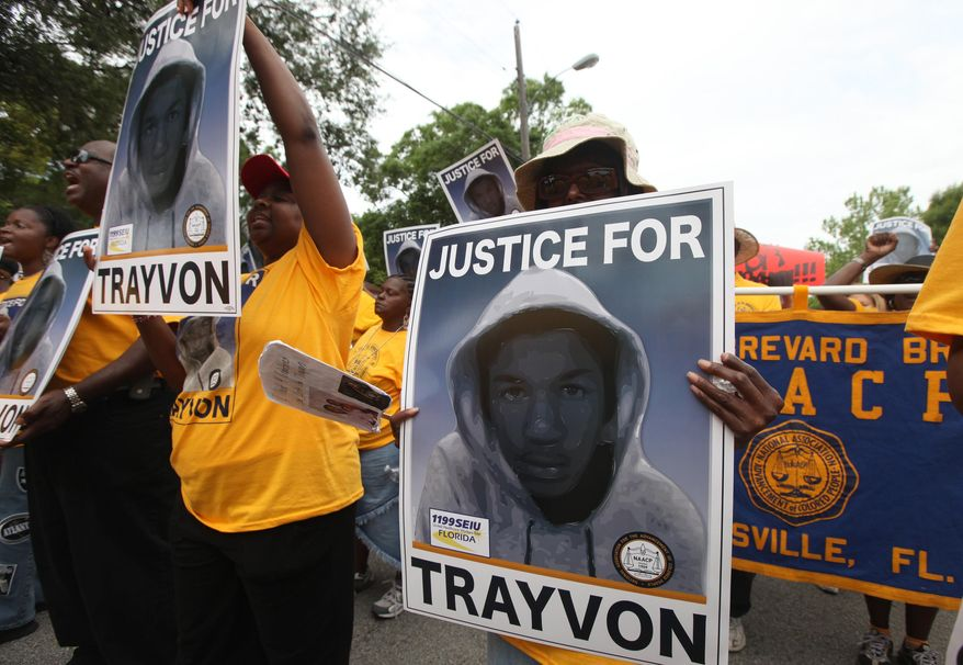 In this March 31, 2012, file photo, protestors hold up signs in a march and rally for slain Florida teenager Trayvon Martin in Sanford, Fla. The death of Martin and later 2013 trial and acquittal of George Zimmerman raised questions about race, gun control and justice in America. (AP Photo/Julie Fletcher, File)