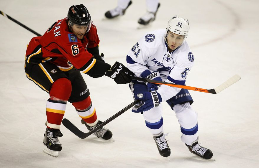 Tampa Bay Lightning's Valtteri Filppula, right, from Finland, gets slashed by Calgary Flames' Dennis Wideman during the first period of an NHL hockey game Friday, Jan. 3, 2014, in Calgary, Alberta. (AP Photo/The Canadian Press, Jeff McIntosh)