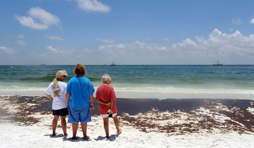 FILE- In this June 23, 2010, file photo, from left, Gina Durell, Island Durell and Linda Harrison of Pensacola, Fla., watch as crews work to clean up oil washed ashore at Pensacola Beach, Fla. Oil from the Deepwater Horizon oil spill off the coast of Louisiana washed up along the Florida Panhandle, hurting the state's tourism season that summer. (AP Photo/ Michael Spooneybarger, File)