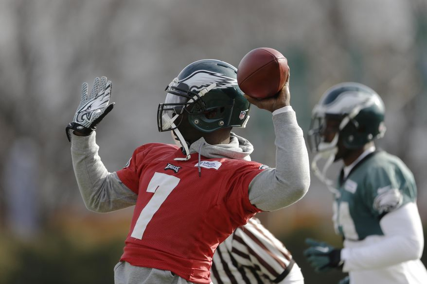 Philadelphia Eagles quarterback Michael Vick throws a pass during NFL football practice at the team's training facility, Tuesday, Dec. 31, 2013, in Philadelphia. (AP Photo/Matt Rourke)