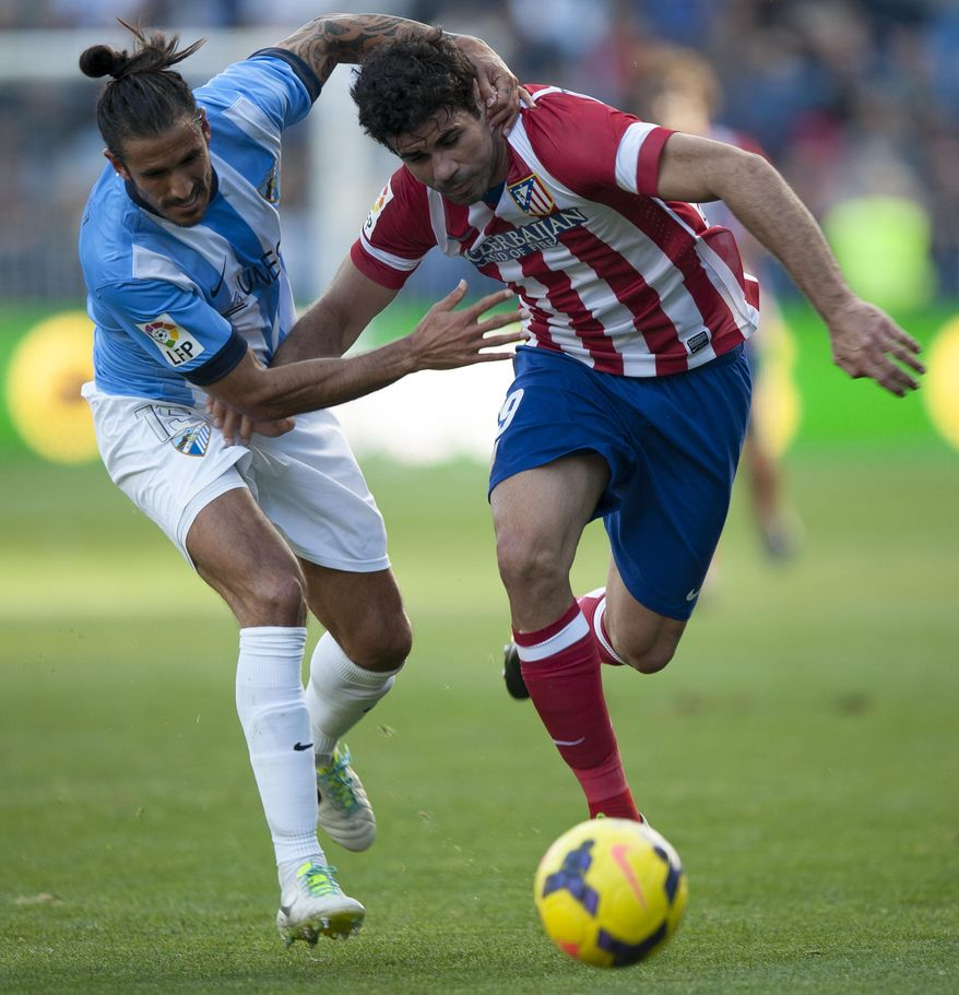 Atletico de Madrid's Diego Costa from Brazil, right, duels for the ball against Malaga''s Marcos Alberto Angeleri from Argentina, left,  during a Spanish La Liga soccer match between Malaga and Atletico de Madrid at the La Rosaleda stadium in Malaga, Spain, Saturday, Jan. 4, 2014. (AP Photo/Daniel Tejedor)