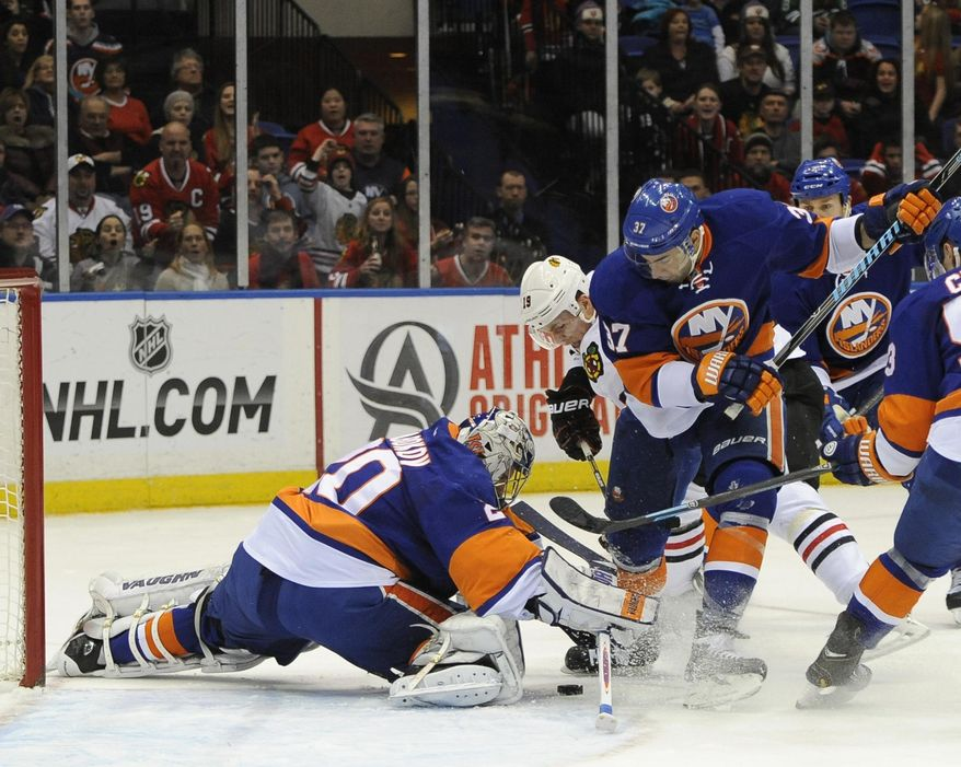 New York Islanders goalie Evgeni Nabokov (20) kicks the puck away from Chicago Blackhawks' Jonathan Toews (19) as Islanders' Brian Strait (37) also defends in the first period of an NHL hockey game on Thursday, Jan. 2, 2014, in Uniondale, N.Y. (AP Photo/Kathy Kmonicek)