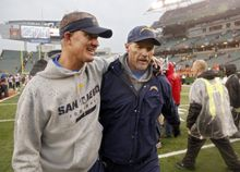 San Diego Chargers head coach Mike McCoy, left, walks off the field with offensive coordinator Ken Whisenhunt after a 27-10 win over the Cincinnati Bengals in an NFL wild-card playoff football game on Sunday, Jan. 5, 2014, in Cincinnati. (AP Photo/David Kohl)