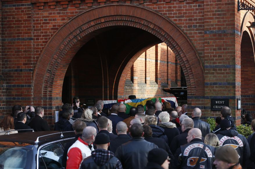 "Mourners carry the coffin of great train robber Ronnie Biggs into the chapel at Golders Green Crematorium in London, Friday Jan. 3, 2014. Biggs was a member of a gang that stole 2.6 million pounds from a Glasgow-to-London mail train in August 1963, in what was called the ""heist of the century."" He spent decades in exile in Brazil before agreeing to return to Britain, and prison, in 2001. (AP Photo/Sang Tan)"