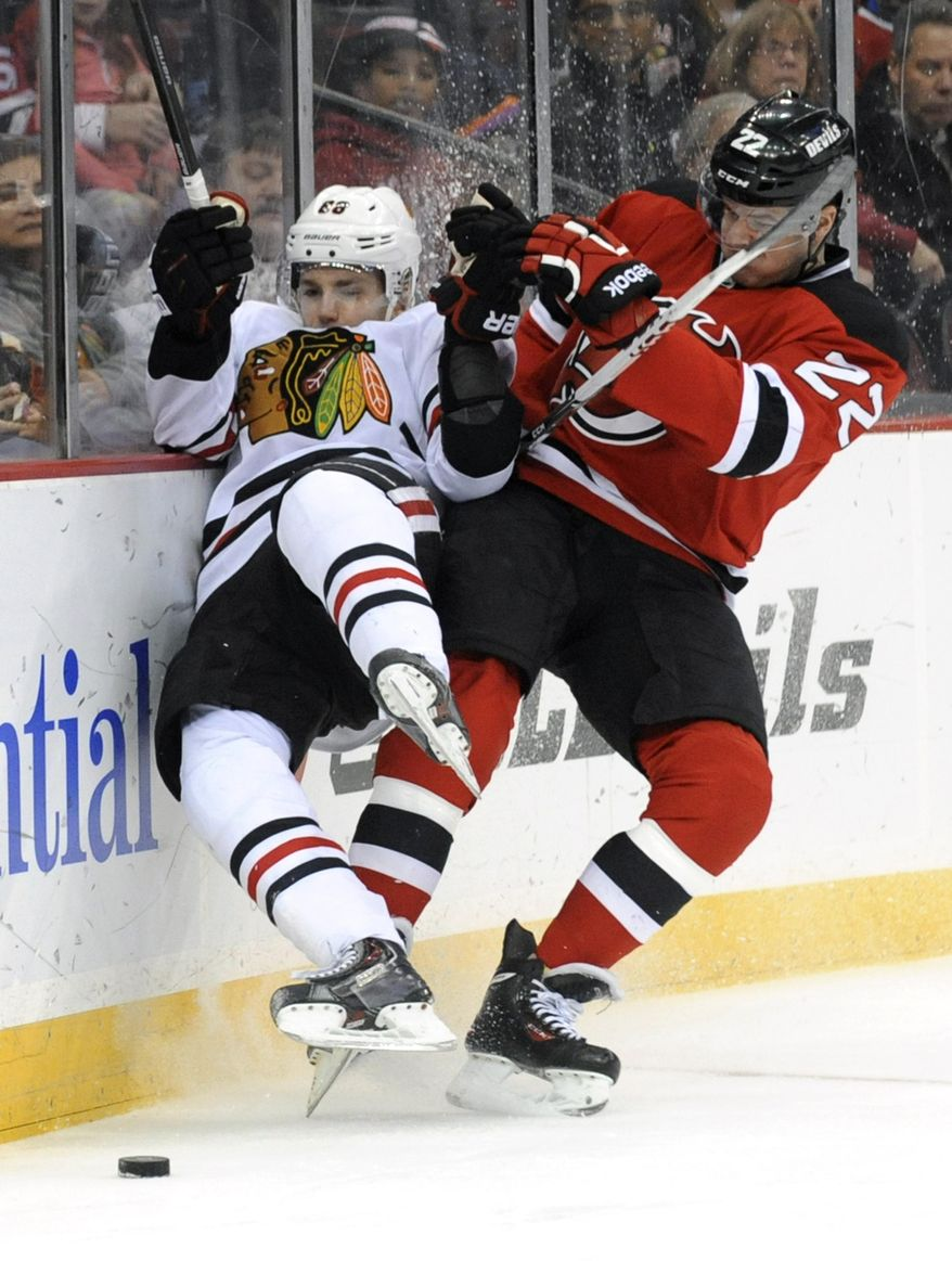 New Jersey Devils' Eric Gelinas, right checks Chicago Blackhawks' Patrick Kane during the first period of an NHL hockey game Friday, Jan. 3, 2014, in Newark, N.J. (AP Photo/Bill Kostroun)