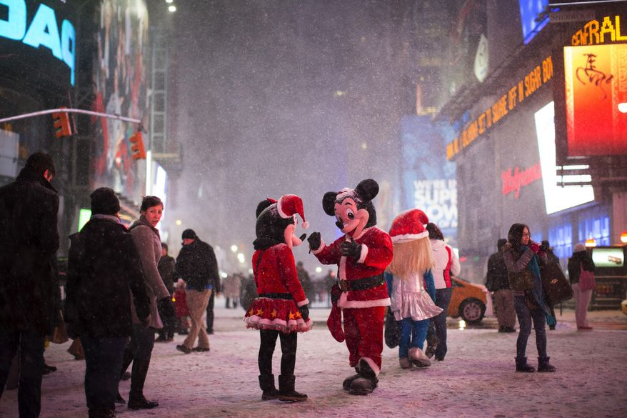 ** FILE ** Two people dressed as Disney characters talk under falling snow in Times Square, Thursday, Jan. 2, 2014, in New York. (AP Photo/John Minchillo)