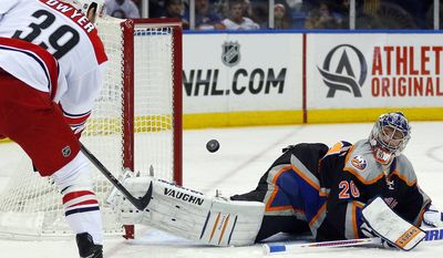 New York Islanders goalie New York Islanders goalie Evgeni Nabokov (20) watches as Carolina Hurricanes right wing Patrick Dwyer (39) shoots past the empty net during the first period of an NHL hockey game on Saturday Jan. 4, 2014, in Uniondale, N.Y. (AP Photo/Paul J. Bereswill)