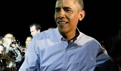 President Barack Obama greets people on the tarmac before boarding Air Force One at Honolulu Joint Base Pearl Harbor-Hickam, in Honolulu, Saturday, Jan. 4, 2014, as he travels back to Washington after their annual family vacation. (AP Photo/Carolyn Kaster)