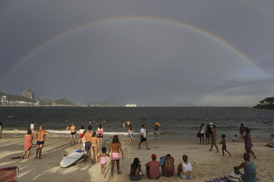 In this Tuesday, Dec. 31, 2013 photo, a rainbow arches across the horizon during New Year's Eve festivities on Copacabana beach in Rio de Janeiro, Brazil. Sugar Loaf is pictured on left. (AP Photo/Leo Correa)
