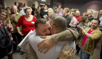 FILE - In this Dec. 20, 2013 file photo, Chris Serrano, left, and Clifton Webb embrace after being married, as people wait in line to get licenses outside of the marriage division of the Salt Lake County Clerk's Office in Salt Lake City. The Supreme Court on Monday, Jan. 6, 2014, put same-sex marriages on hold in Utah, at least while a federal appeals court more fully considers the issue.  (AP Photo/Kim Raff, File)