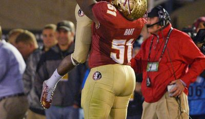 Florida State's Bobby Hart holds up Levonte Whitfield after Whitfield's 100-yard run back of a kickoff during the second half of the NCAA BCS National Championship college football game against Auburn Monday, Jan. 6, 2014, in Pasadena, Calif. (AP Photo/Mark J. Terrill)