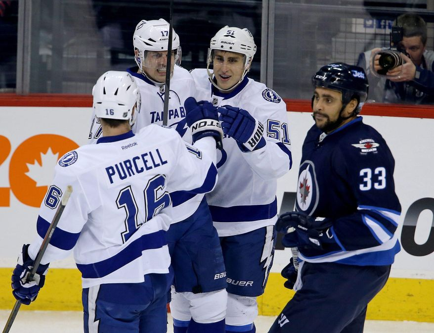 Tampa Bay Lightning's Teddy Purcell (16), Alex Killorn (17) and Valtteri Filppula (51) celebrate Filpula's goal against the Winnipeg Jets as Jets' Dustin Byfuglien (33) skates past during the first period of an NHL hockey game Tuesday, Jan. 7, 2014, in Winnipeg, Manitoba. (AP Photo/The Canadian Press, Trevor Hagan)